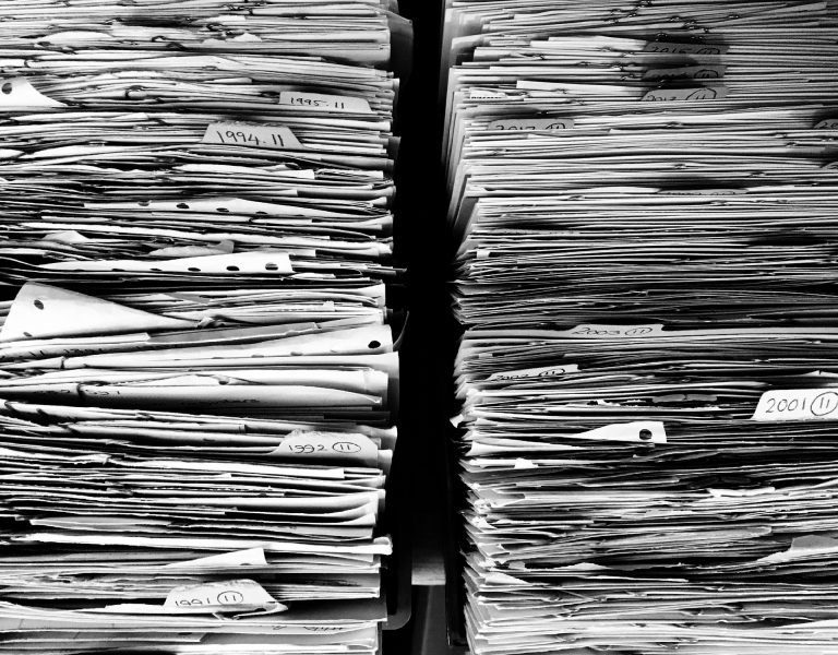 Two stacks of paper files next to each other in black and white